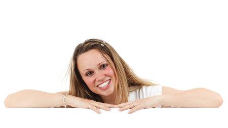 Uśmiechnięta dziewczyna opiera się o stół