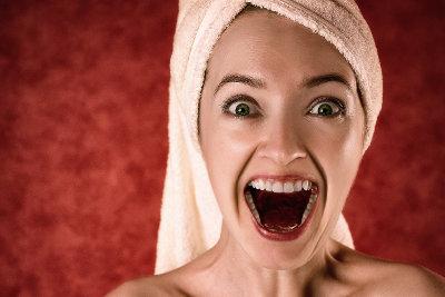 Kobieta z ręcznikiem na głowie otwiera usta ze zdziwienia