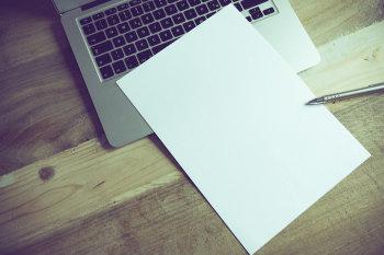 Laptop leży na stole a na nim znajdują się dokumenty