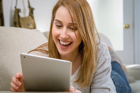 Dziewczyna trzyma tablet i przegląda strony internetowe