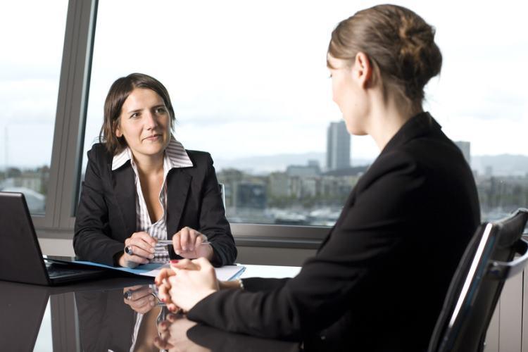 Dwie kobiety rozmawiają przy stole konferencyjnym w firmie.