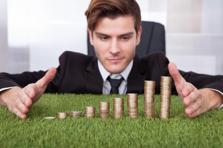 Mężczyzna wpatruje się w rozłożone na stole monety