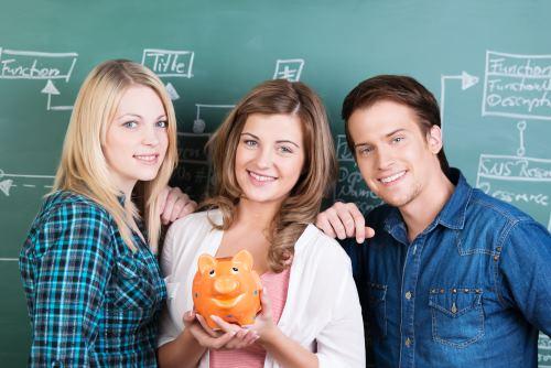 Studenci stoją przed tablicą do pisania kredą i trzymają w dłoni skarbonkę