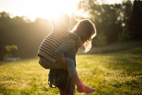 Mama trzyma dziecko na barana i stoją w promieniach słońca