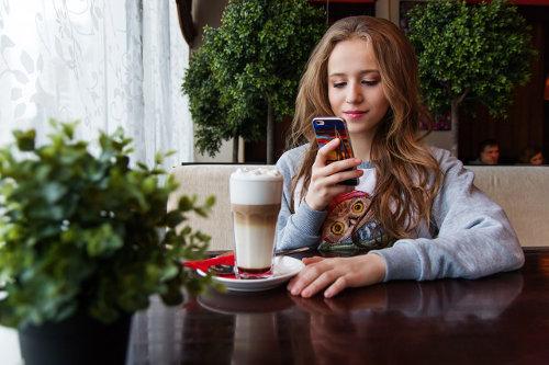 Dziewczyna siedzi przy stoliku z kawą i pisze wiadomość sms