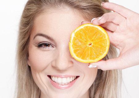 Kobieta przykłada sobie od oka połówkę pomarańczy i się uśmiecha