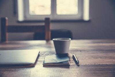 Filiżanka kawy, długopis i notes znajdują się obok siebie na stoliku