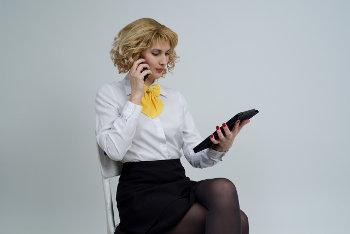 Kobieta ubrana na galowo siedzi na fotelu, rozmawia przez telefon i przegląda tablet