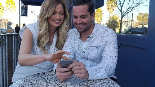 Małżeństwo siedzi przy stoliku w kawiarni i razem spoglądają na telefon komórkowy