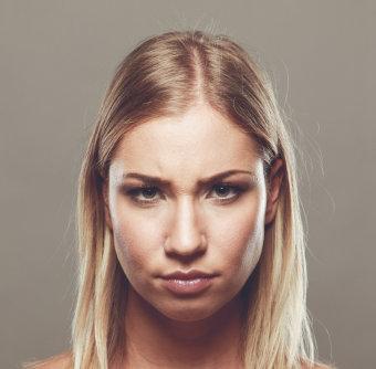 Twarz kobiety wyrażająca niezadowolenie