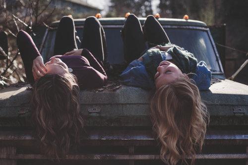 Dwie dziewczyny leżą na masce samochodu