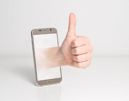 Dłoń z wystawionym kciukiem wychodzi z ekranu telefonu komórkowego