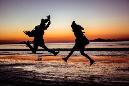 Dwoje ludzi podskakuje na brzegu morze w blasku zachodzącego słońca