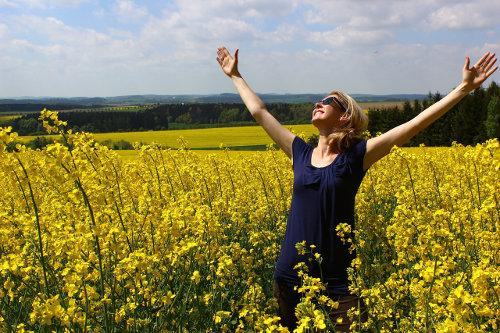 Kobieta stoi w polu pełnym rzepaku z rękami uniesionymi w górę