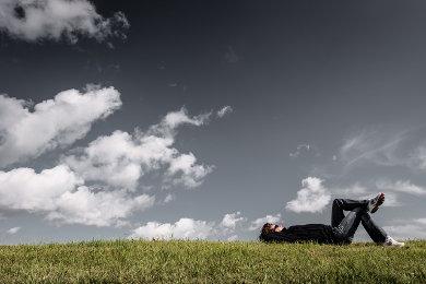 Mężczyzna leży na plecach na zielonej łące