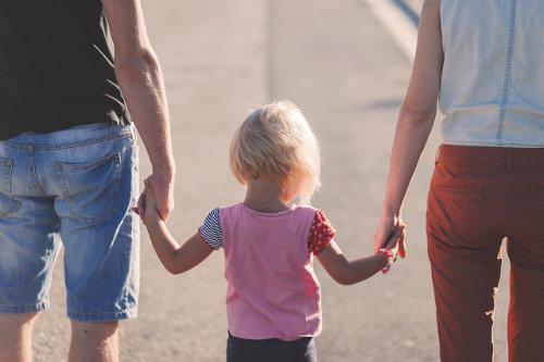 Matka i ojciec trzymają dziecko za ręce i idą z nim na spacer