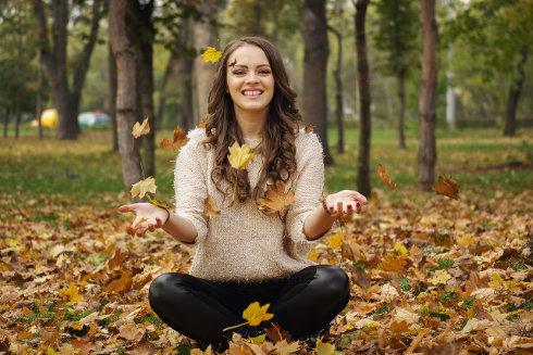 Kobieta siedzi na kupce z opadłych liści i je podrzuca