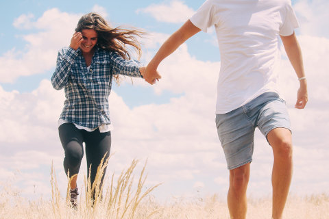 Młode małżeństwo spaceruje po piasku na plaży trzymając się za ręce