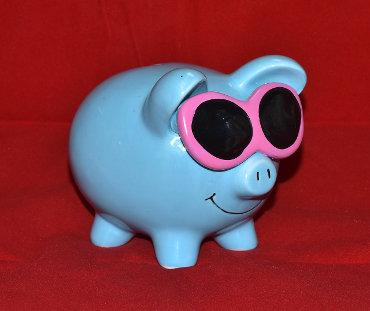 Niebieska skarbonka świnka w różowych okularach