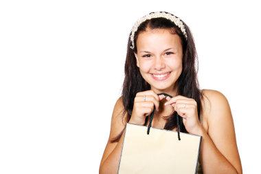 Dziewczyna przyciska do piersi torebkę z prezentem