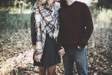 Mężczyzna i kobieta na jesiennym spacerze trzymają się za ręce