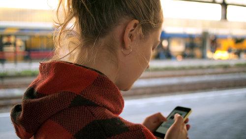 Kobieta w kurtce w kratkę piszę smsa
