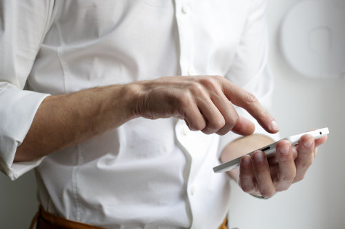 Mężczyzna w białej koszuli używa telefon komórkowy
