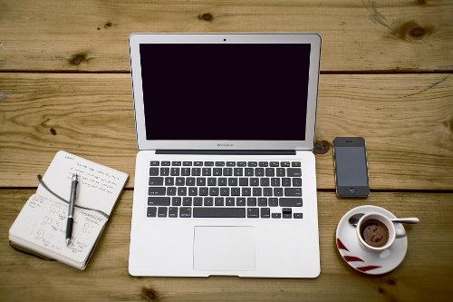 Laptop na stole obok filiżanki kawy i notesu