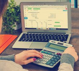 Kobieta siedzi przy laptopie i liczy coś na kalkulatorze