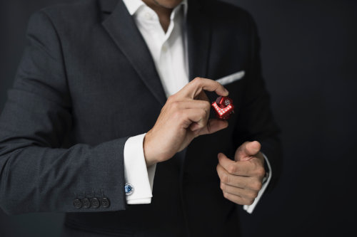 Mężczyzna w marynarce trzyma w dłoni czerwoną kostkę do gry