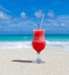 Kieliszek z napojem i słomką na piasku na plaży
